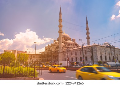 Yeni Cami Ottoman imperial mosque located in the Eminönü quarter of Istanbul, Turkey. Sunset cloudy sky in background and taxi cabs in foreground.