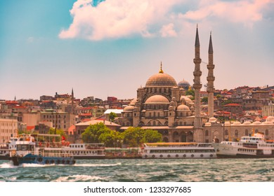 Yeni Cami Ottoman imperial mosque located in the Eminönü quarter of Istanbul, Turkey. Strait of Bosporus with ships in foreground and blue cloudy sky in background.