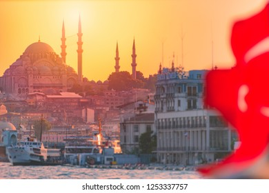 Yeni Cami Ottoman imperial mosque located in the Eminönü quarter of Istanbul, Turkey. Sunset sky in background, sea port in foreground.