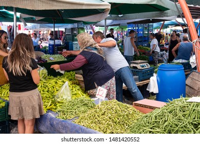 Yenifoca, Foca, Izmir, Turkey - Aug 7th, 2019 - Market stall at weekly farmers market in Yenifoca. Locals buying fresh vegetables. Green peppers, green beans and okra (also known as lady fingers)