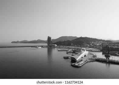 Yeosu, South Korea - Yeosu expo port ferris wheel and modern exhibition halls with mountain in background