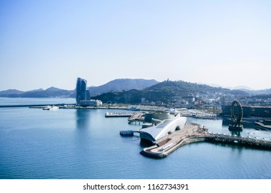 Yeosu, South Korea - Yeosu expo port ferris wheel and modern exhibition halls with mountain in background