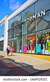 Yeovil, Somerset / England - 7/21/2019: The modern front elevation of the Topshop and Topman shops in the Quedam Centre Yeovil. Ladies & mens fashion retailers. Woman & young daughter passing store.