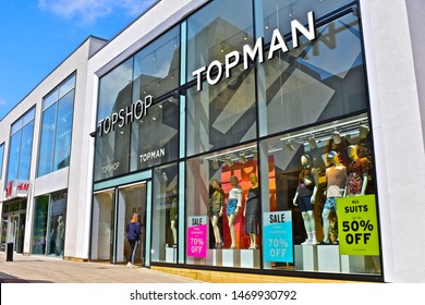 Yeovil, Somerset / England - 7/21/2019: The modern front elevation of the Topshop and Topman shops in the Quedam Centre Yeovil. Ladies & mens fashion retailer. Young woman entering store.