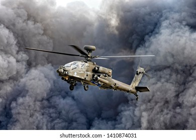 Yeovilton, Somerset / UK - July 11 2015: An AgustaWestland Apache AH1 helicopter hovers in front of a black smoke cloud during the Commando Assault Finale at the RNAS Yeovilton International Airday