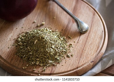 Yerba mate with calabash and metall bombija on the wooden board and gray tissue