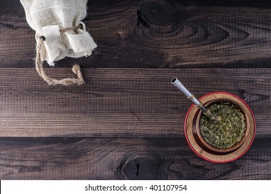 Yerba mate in ceramic matero with bombilla and linen bag on wooden table. Top view.