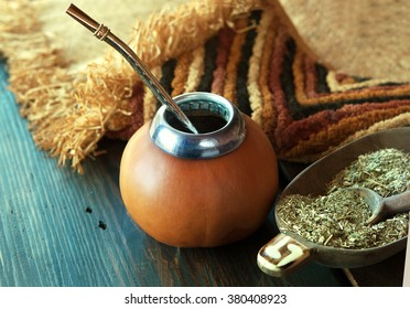 Yerba mate-South American tea, dried leaves in wooden bowl with a wooden mate calabash with tea