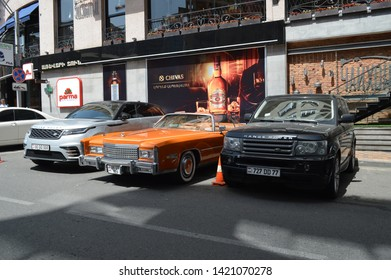 Yerevan, Armenia - 01 June 2019. Fully restored orange 70's Cadillac Eldorado in perfect condition standing between two modern Range Rovers at cafe parking under bright sun.