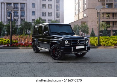 "Yerevan, Armenia - 04 June 2019. Black stock Mercedes G63 AMG with ""Edition 1"" side stripes standing at famous hotel's parking under bright sun with green trees."