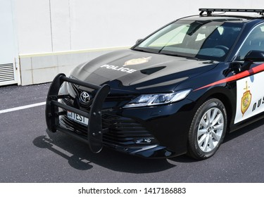 Yerevan, Armenia - 04 June 2019. Armenian's new police car - Toyota Camry. Black car with red and white stickers standing next to bright background.