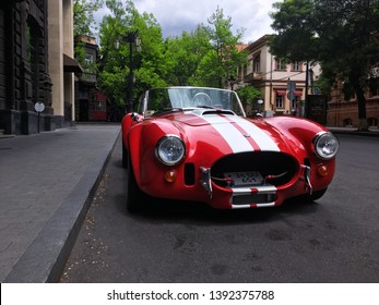 Yerevan, Armenia - 08 May 2019. Red classic american sport car AC Cobra with white stripes and in perfect condition standing in the city centre parking under bright sun.