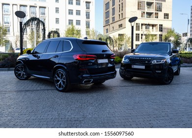 Yerevan, Armenia - 08 November 2019. Two black cars: new 2019 BMW X5 and Range Rover Sport stands at beautiful car parking surrounded with flowers and green grass.