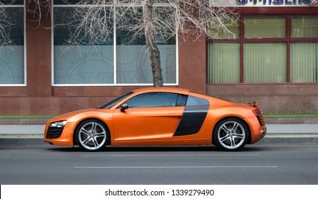 Yerevan, Armenia - 10 March 2019. Matte orange german sport car Audi R8 parked at one of central streets of Yerevan under bright spring sun.