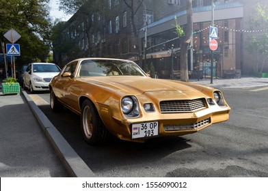 Yerevan, Armenia - 10 November 2019. Champagne gold old school muscle car Chevrolet Camaro in good condition stands at central street parking under shiny autumn sun.