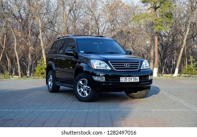 Yerevan, Armenia - 12 January 2019. Black obsidian black suv Lexus GX in the middle of city park's car parking. Big black car surrounded with leafless trees.