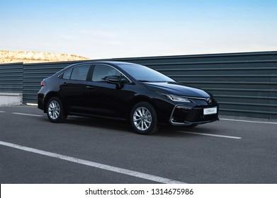 Yerevan, Armenia - 14 February 2019. All-new Toyota Corolla arrived to dealership in Yerevan. Black gloss car waith dealer's license plate on the road near dark green fence.