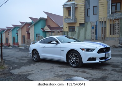 Yerevan, Armenia - 15 February 2019. Pearl white american muscle car Ford Mustang GT with blue stripes near modern houses in the uptown.