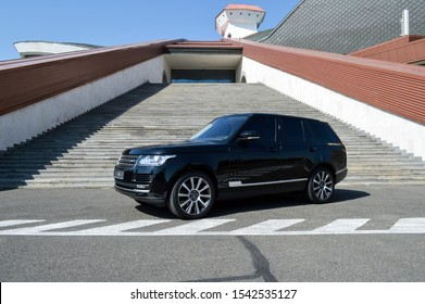 Yerevan, Armenia - 15 October 2019. Different sides of black Range Rover with black tinted windows stand at car parking with beautiful building on the background.