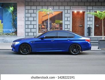 Yerevan, Armenia - 18 June 2019. Dark blue sport car BMW M5 with black wheels standing next to luxury shops at Northern Avenue.