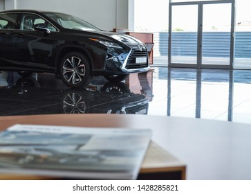 Yerevan, Armenia - 18 June 2019. Black Lexus RX350 in the dealership's showroom and branded Lexus catalogue in wooden case.