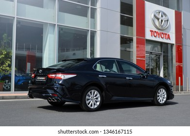 Yerevan, Armenia - 20 March 2019. Toyota Camry modified by Khann tuning atelier standing next to main entrance of Toyota Yerevan dealership. Black car and bright sun.