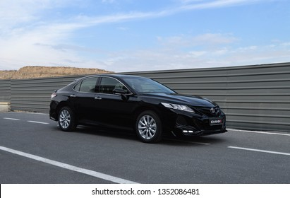 Yerevan, Armenia - 20 March 2019. Toyota Camry modified by Khann tuning atelier standing near of Toyota Yerevan dealership. Black car and bright sun