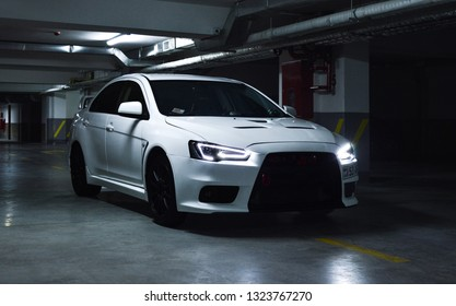 Yerevan, Armenia - 22 February 2019. Pretty white Mitsubishi Lancer Evolucion X with lot of modifications and turned on LED lights at dark and grey underground parking.