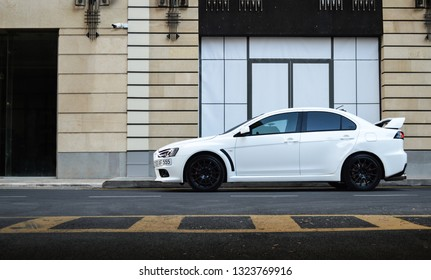 Yerevan, Armenia - 22 February 2019. Pearl white Mitsubishi Lancer Evolucion X with lot of modifications and turned on LED lights at city centre parking near luxury buildings.