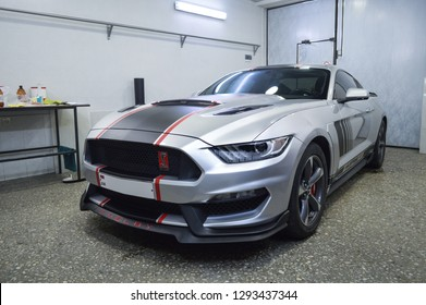 Yerevan, Armenia - 22 January 2019. Silver sport car Ford Mustang with Shelby bodykit standing in the wrapping workshop after it gets black and red stripes on body.