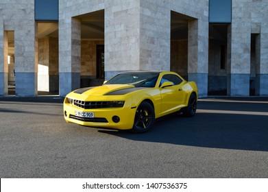 Yerevan, Armenia - 22 May 2019. Bright yellow Chevrolet Camaro with black stripes standing at car parking near luxury hotel under bright sun.