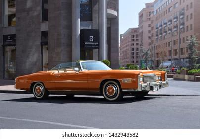 Yerevan, Armenia - 23 June 2019. Classic american car: orange and fully restored Cadillac Eldorado standing at Northern Avenue under bright sun near watch store.