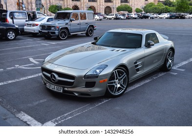Yerevan, Armenia - 23 June 2019. Grey sport car Mercedes-Benz SLS AMG standing at Republic Square near grey G63 AMG on the clean asphalt.