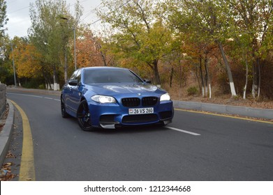 Yerevan, Armenia - 24 October 2018. Powerful beast BMW M5 in blue color, with carbon fiber elements standing in the city park surrounded with green and yellow trees. Beautiful autumn and crazy car.