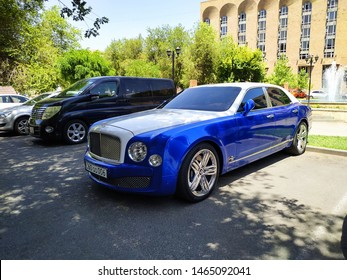 Yerevan, Armenia - 27 July 2019. Two tone luxury sedan Bentley Mulsanne in silver and blue colors standing at car parking near green trees.