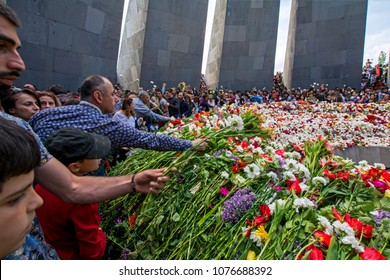 Yerevan, Armenia - April 24, 2018: Armenians laying flowers at the eternal flame in the center of the twelve slabs  of Armenian Genocide memorial on anniversary of Armenian Genocide of 1915