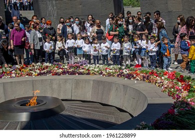 Yerevan, Armenia - April 24, 2021: Armenians laying flowers at the eternal flame in the center of the twelve slabs of Armenian Genocide memorial on anniversary of Armenian Genocide of 1915