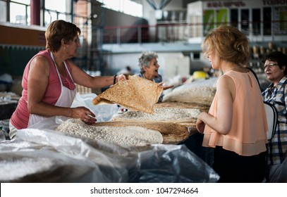 Yerevan, Armenia - August 16, 2017: Armenian woman selling traditional Armenian lavash bread to tourists at a local market in Yerevan