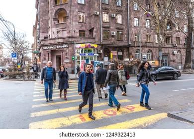 Yerevan, Armenia - Jan 18th 2018 - Group of people crossing a road in downtown Yerevan the capital of Armenia
