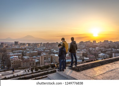 Yerevan, Armenia - Jan 8th 2018 - Locals watching the sunset at the top of the Cascade with Yerevan city in the background
