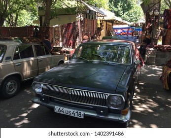 Yerevan, Armenia, May 2018: An old vintage black car is parked in one of the  alleys of Vernissage Market among traditional Armenian carpets  in Yerevan, capital of Armenia.