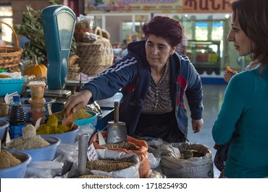 Yerevan, Armenia, October 2012: An Armenian woman carrying a small baby tries different saffron and herbs at a spices stall in Yerevan Central Food Market, Armenia