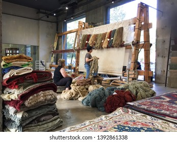 Yerevan, Armenia, September 2018: Two women  choosing wool and its colours to start a new artisanal carpet in a traditional loom , at the workshop of Tufenkian Carpets in Yerevan.