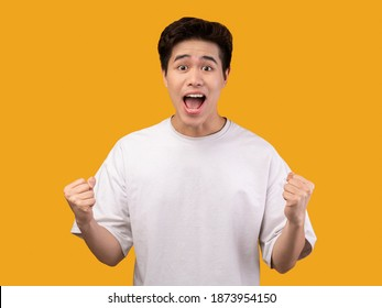 Yes, Achievement Concept. Excited young asian man cheering and screaming, celebrating victory. Emotional overwhelmed guy yelling and shaking clenched fists, isolated over orange background