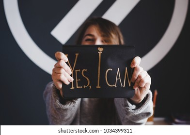 Yes I can! Girl with motivation words. Words written by gold pen on black paper. Success and inspiration. Believe in yourself. Yes, you can! Don't give up! Beautiful girl with sign.