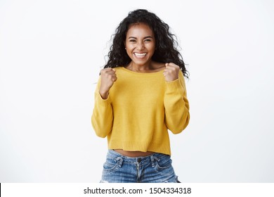 Yes deal mine. Successful african-american cute woman in yellow sweater, smiling happily, celebrating amazing news, making fist pump reacting lucky excellent opportunity, standing white background