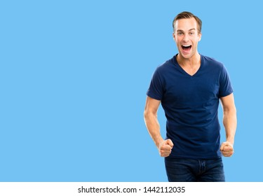 Yes, I did it! Very happy young man, isolated over blue color background. Emotions and success concept. Excited male model with open mouth, in blue smart casual wear at studio picture. Copy space.