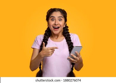 Yes, Great News. Portrait Of Excited Indian Woman Celebrating Win, Using Smartphone And Pointing At Gadget, Smiling Young Lady Having Success, Holding Cellphone, Yellow Studio Background
