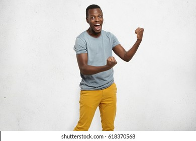 Yes! Handsome young Afro-American man employee feeling excited, gesturing actively, keeping fists clenched, exclaiming joyfully with mouth wide opened, happy with good luck or promotion at work