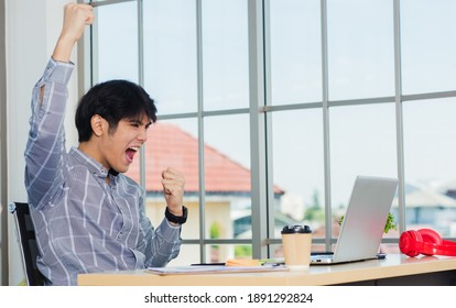 Yes! Happy excited Asian man raising his arm up to celebrate celebrating success. Young businessman using laptop computer at office desk he glad to receive good winner profits from the job